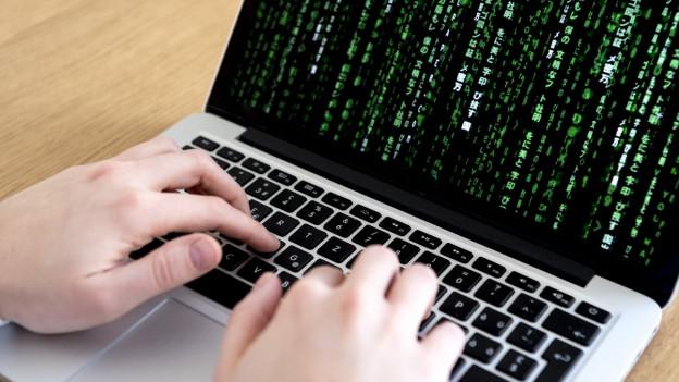 Zwei Hände über einer Laptop-Tastatur - über den Bildschirm flimmern grüne Zeichen