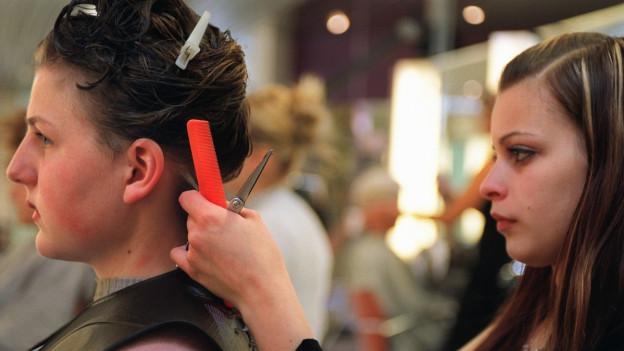 Eine Lernende schneidet einer Kundin im Coiffeur Salon die Haare