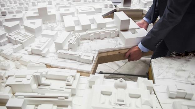 Zwei Hände setzten das umgebaute Hochschulquartier ins Stadtmodell ein