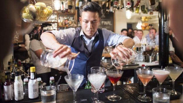 Mann mixt hinter einer Bar Drinks, verschiedene Gläser vor ihm