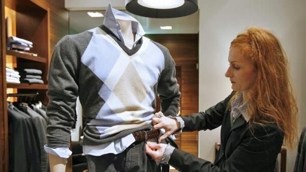 Eine Mode-Verkäuferin zupft ein Hemd an einer Schaufensterpuppe zurecht.