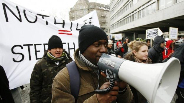 """schwarzer Mann mit Megaphon, hinter ihm ein weisses Transparent mit der Aufschrift """"Nothilfe = Sterbehilfe"""""""