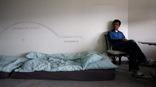 Ein dunkelhäutiger Mann sitzt neben einer Matratze.