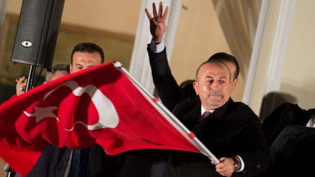 Der türkische Aussenminister schwenkt die türkische Flagge an einer Veranstaltung.