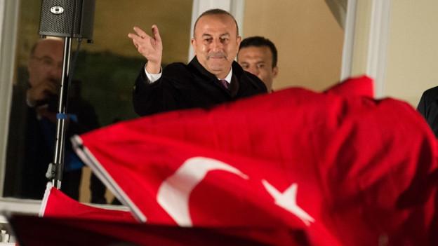 Eine rote Fahne mit Halbmond und Stern, dahinter ein Mann der winkt.