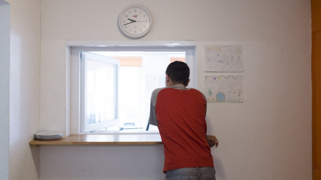 Ein minderjähriger Flüchtling schaut verträumt aus dem Fenster.