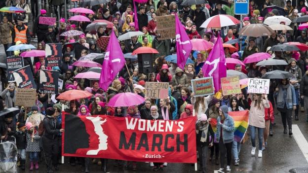 Frauen mit Schirmen und Transparenten demonstrieren für Gleichberechtigung.