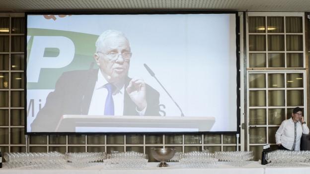 Ein grosser Bildschirm zeigt einen Mann bei einer Rede.