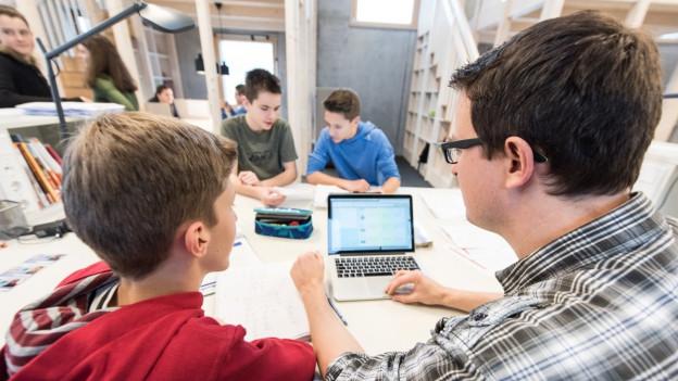 Ein Schüler und ein Lehrer sitzen vor einem Laptop.