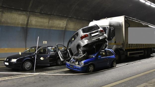 Ein Auto steht im Tunnel auf dem Dach eines anderen, ein Lastwagen ist in die Fahrzeuge verkeilt