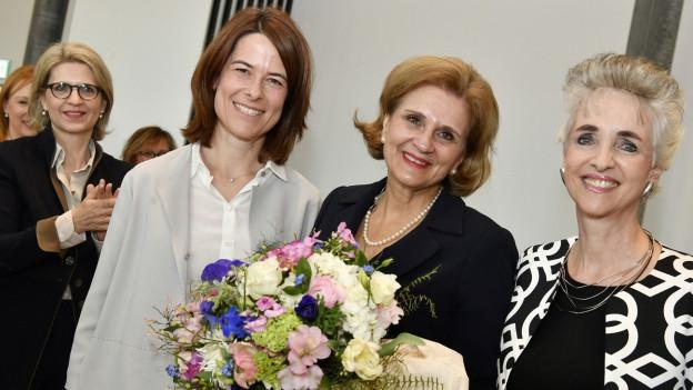 Drei Frauen, eine davon mit Blumenstrauss.