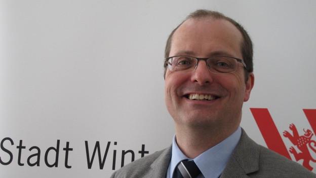 Ein Mann mit Brille lacht.