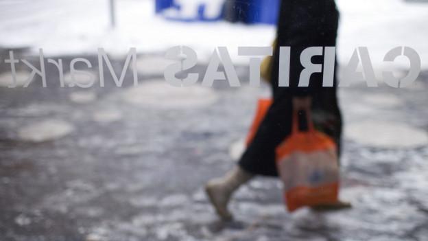 Eine Frau mit Einkaufstaschen geht auf einer Strasse, fotografiert durch eine Glasscheibe.