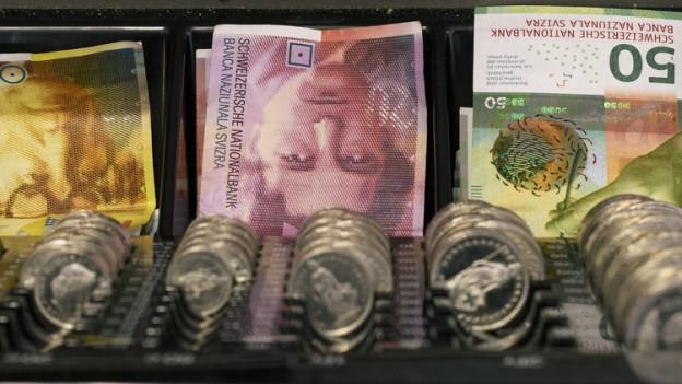 Offene Kasse mit Geldstücken und Banknoten