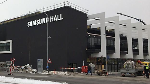 Halle im Winter mit Baustellenabschrankungen und Baustellenfahrzeugen davor