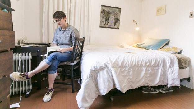 Eine Frau sitzt in ihrem Zimmer und liest ein Buch.