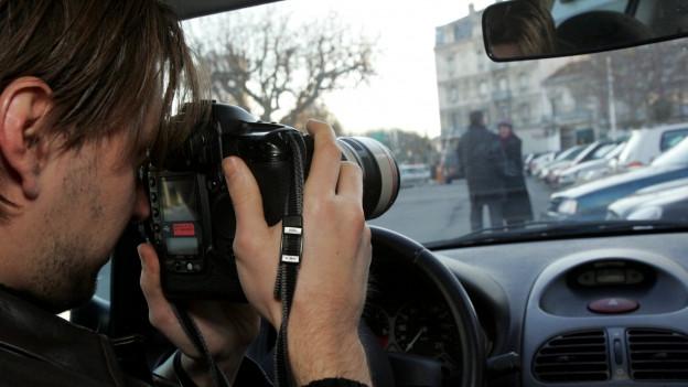 Ein Mann fotografiert ein Paar auf der Strasse vom Auto aus.