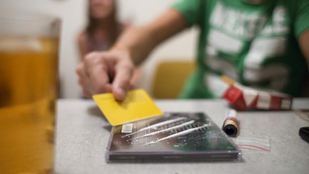 Ein Mann teilt das Kokain in drei feine Linien auf.