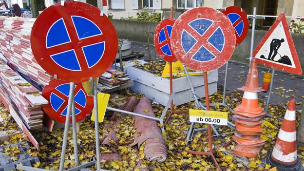 Halteverbotstafeln und andere Baustellenabschrankungen stehen an einer Quartierstrasse bereit.