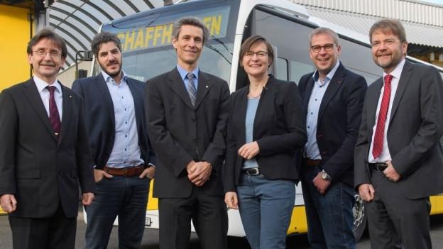 Der versammelte fünfköpfige Stadtrat Schaffhausen vor einem Stadtbus.
