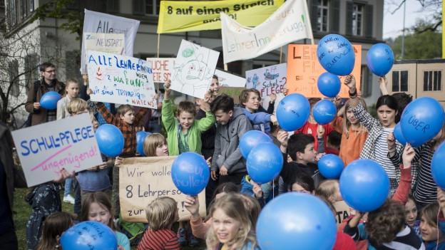 Kinder und Erwachsene demonstrieren mit Plakaten und Ballonen.