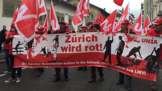 """Männer mit Schutzhelmen und Unia-Fahnen halten ein Transparent mit dem Slogan """"Zürich wird rot""""."""