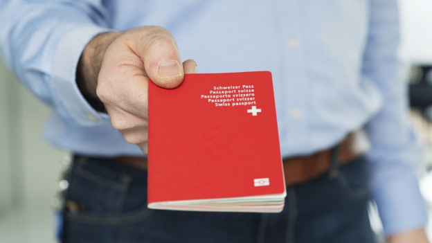 Ein Mann übergibt seinem Gegenüber einen Schweizer Pass.