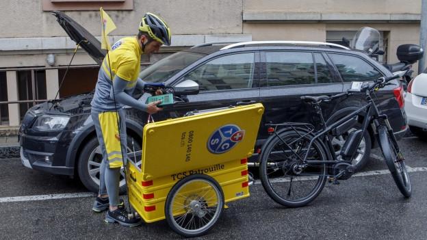 Junger Mann steht zwischen einem E-Bike mit gelbem Anhänger und einem Auto mit geöffneter Motorhaube.