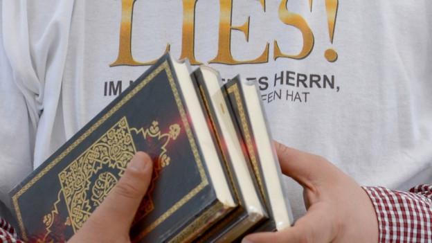 Ein Mann hält den Koran in seinen Händen.