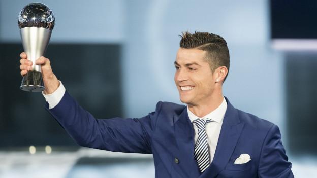 Der Fussballer Cristiano Ronaldo hält eine Trophäe in den Händen.