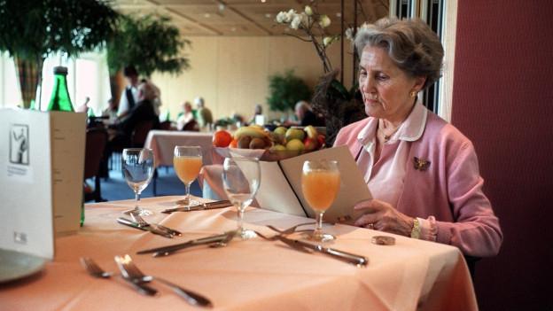 Eine Frau in einem Altersheim sitzt am Tisch und isst.