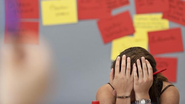Eine jugendliche Schülerin stützt den Kopf auf beide Hände, im Hintergrund eine Tafel mit gelben und roten Notizzetteln drauf.