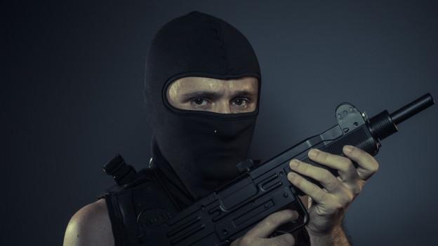 Ein Mann mit Sturmhaube und «Maschinengewehr» (Symbolbild)