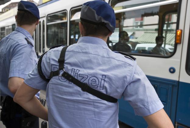 Zwei Polizisten in Uniform vor einem Zürcher Tram