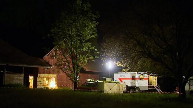 Ein Truck und Zelte der Polizei stehen im Scheinwerferlicht vor einer Scheune.