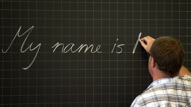 Ein Schüler schreibt einen Text auf eine Wandtafel