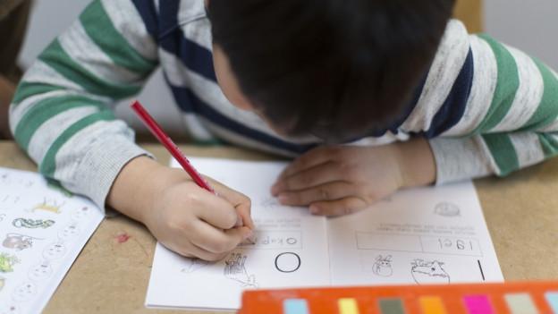 Kind schreibt an einem Tisch.