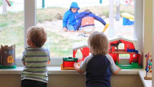 Zwei kleine Buben schauen aus dem Fenster