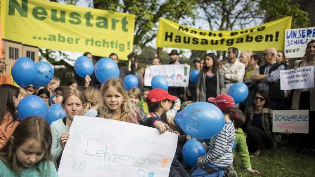 Kundgebung von Schülern und Eltern mit Transparenten und Ballonen.