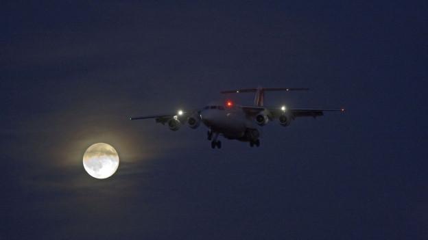 Ein Flugzeug vor dem Vollmond