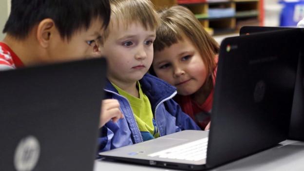 Drei Kinder im Primarschulalter sitzen vor einem Computer