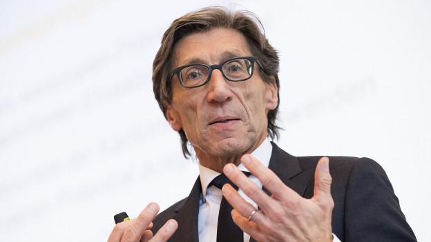 Ein Mann mit Brille und dichtem Haar gestikuliert.