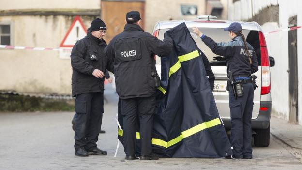 Polizisten vor dem Haus, in dem die Bluttat geschah