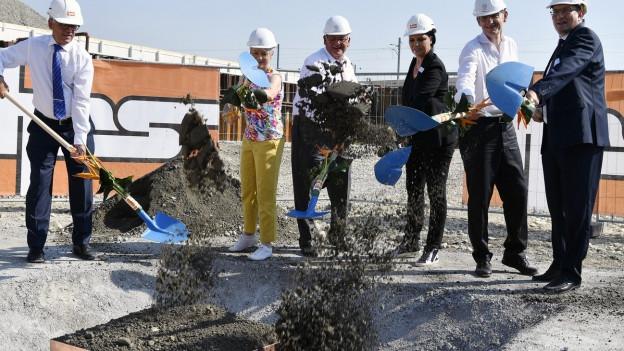 5 Frauen und Männer mit weissen Bauhelmen und Schaufeln schütten Erde auf eine Box.