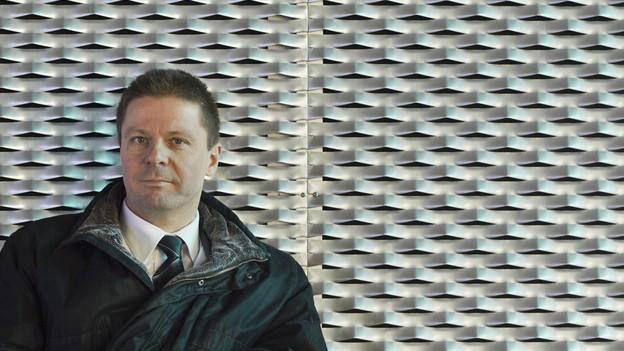 Mann mit kurzen Haaren vor silbergrauem Hintergrund