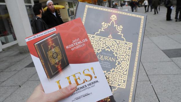 eine Hand hält einen Flyer der Aktion Lies! und einen Koran