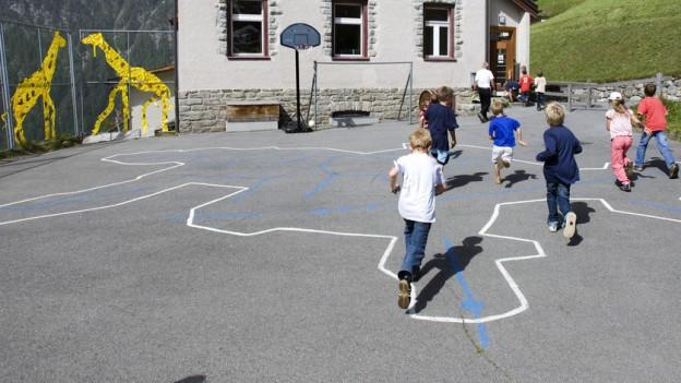Kinder spielen auf dem Sportplatz