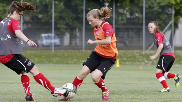 Zwei junge Frauen spielen Fussball im Training.