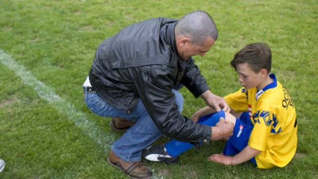 Ein Mann bindet seinem Sohn im Fussballdress den Schuh