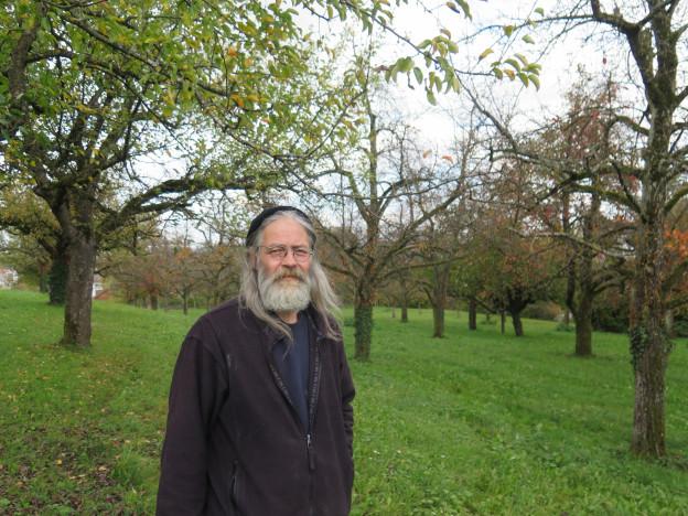 Ein Mann steht vor einem grossen Baum